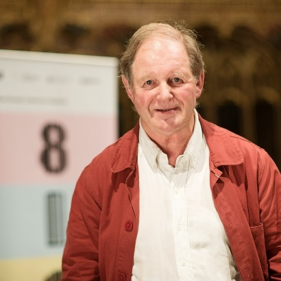 Image of author Michael Morpurgo standing and smiling on stage at MLF 18