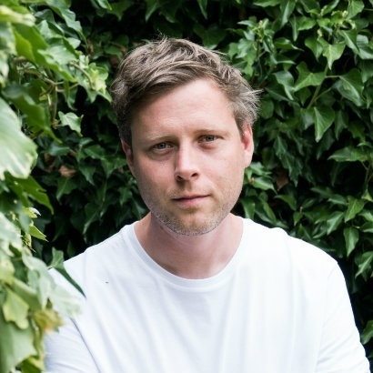 Headshot of author Max Porter against a background of greenery
