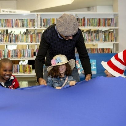 Children holding on to a parachute as part of story time