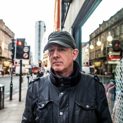 Headshot of DJ and author Dave Haslam in the street