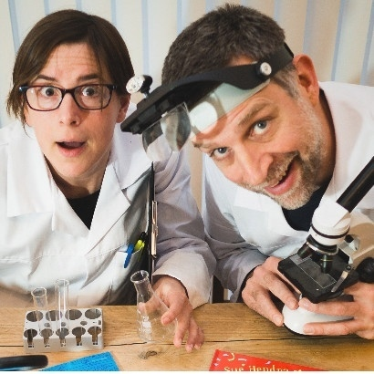 Photo of authors Sue Henra and Paul Linnet dressed as scientists and holding test tubes and science equipment