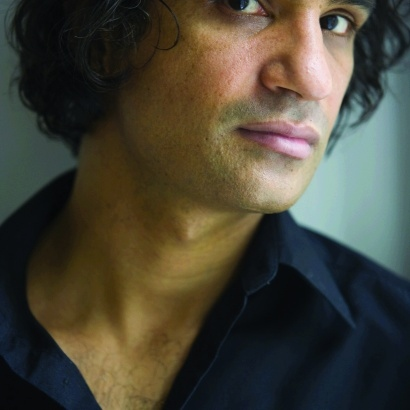 Close-up portrait of writer Nadeem Aslam looking pensive in a black shirt