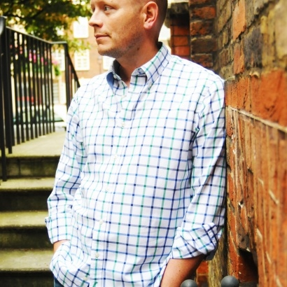 Acclaimed Young Adult author Patrick Ness leaning against a brick wall in jeans and a blue and white checked shirt.