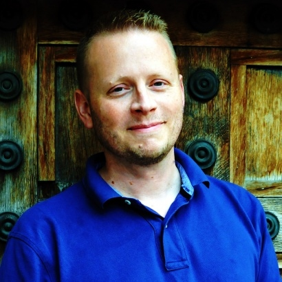 Acclaimed Young Adult author Patrick Ness in a royal blue top, standing infront of an elaborate wooden wall.