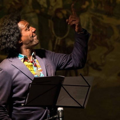 Lemn Sissay performing at Town Hall pointing at ceiling