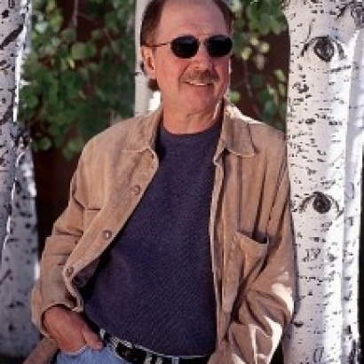 Mystery and action thriller writer David Morrell looking like a detective in sunglasses, blue jeans, sweater and jacket.