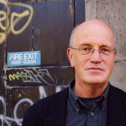 Cult author and psychogeographer Iain Sinclair infront of an old, grafffitied wall.