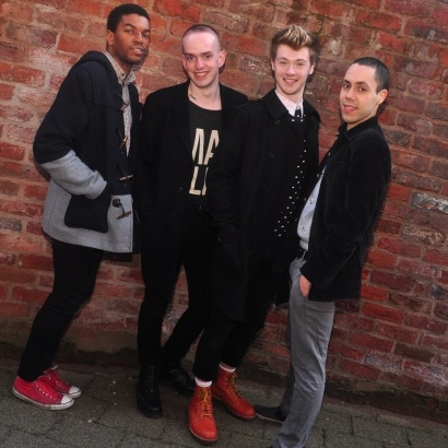 Group of 4 young queer performers and writers against a brick wall