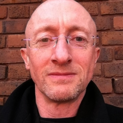 Close-up portrait of author Nicholas Royle standing infront of a brick wall