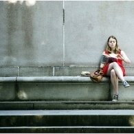 A picture of a girl in a red dress leaning against a wall reading a book