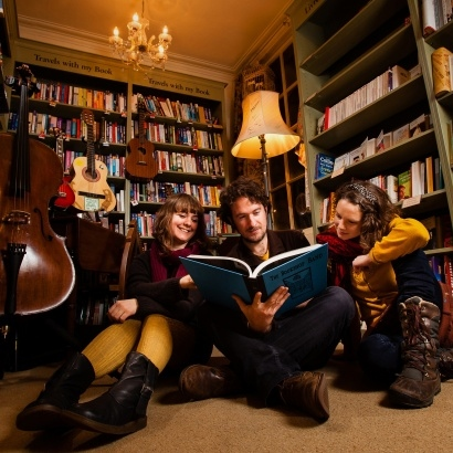 A picture of the musical trio the bookshop band reading a book