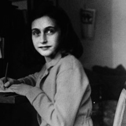 Photograph of a young Anne Frank writing at her desk