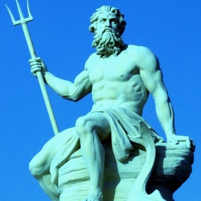 A statue of Poseidon against a backdrop of a sunny day